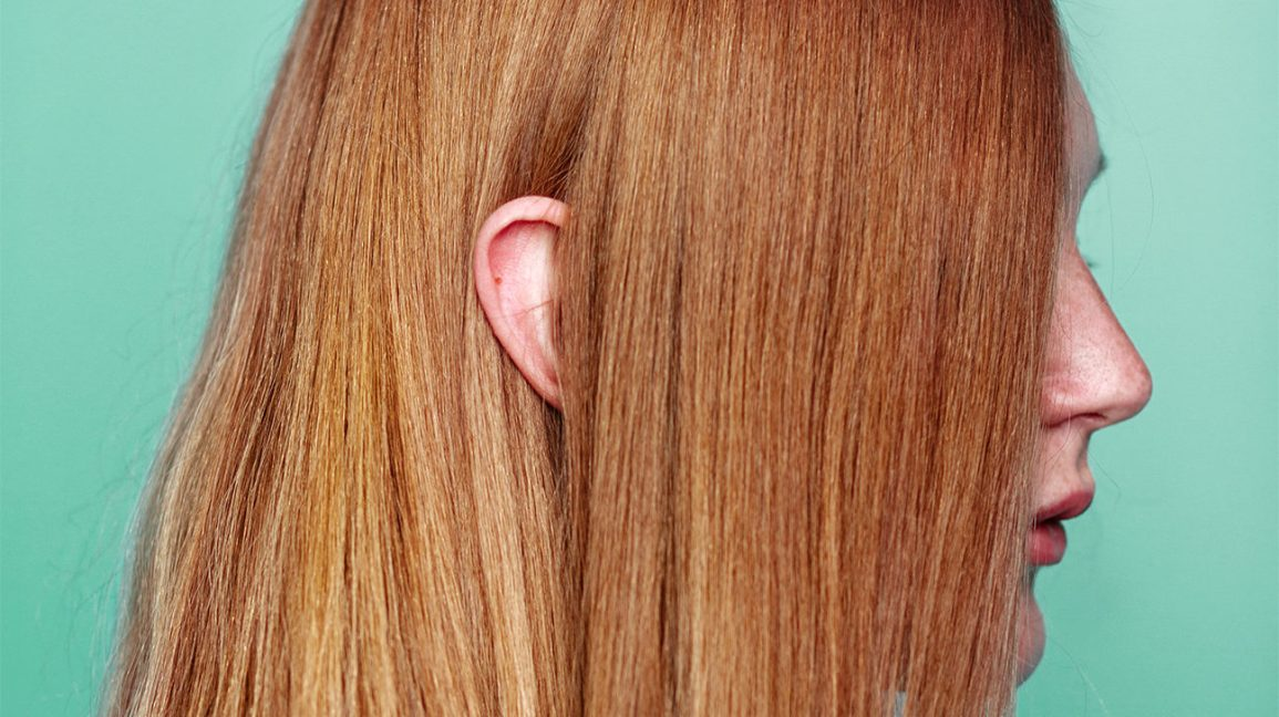 Profile view of red headed girl with her ear peeking through her hair.