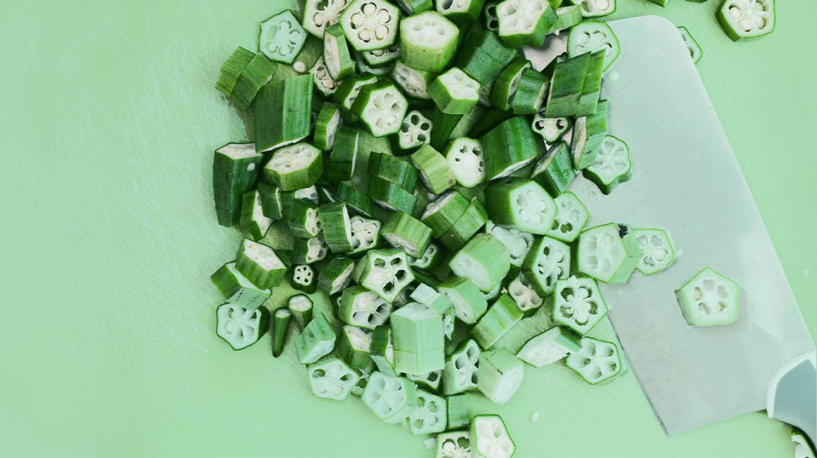 Chopped okra on a lime green background