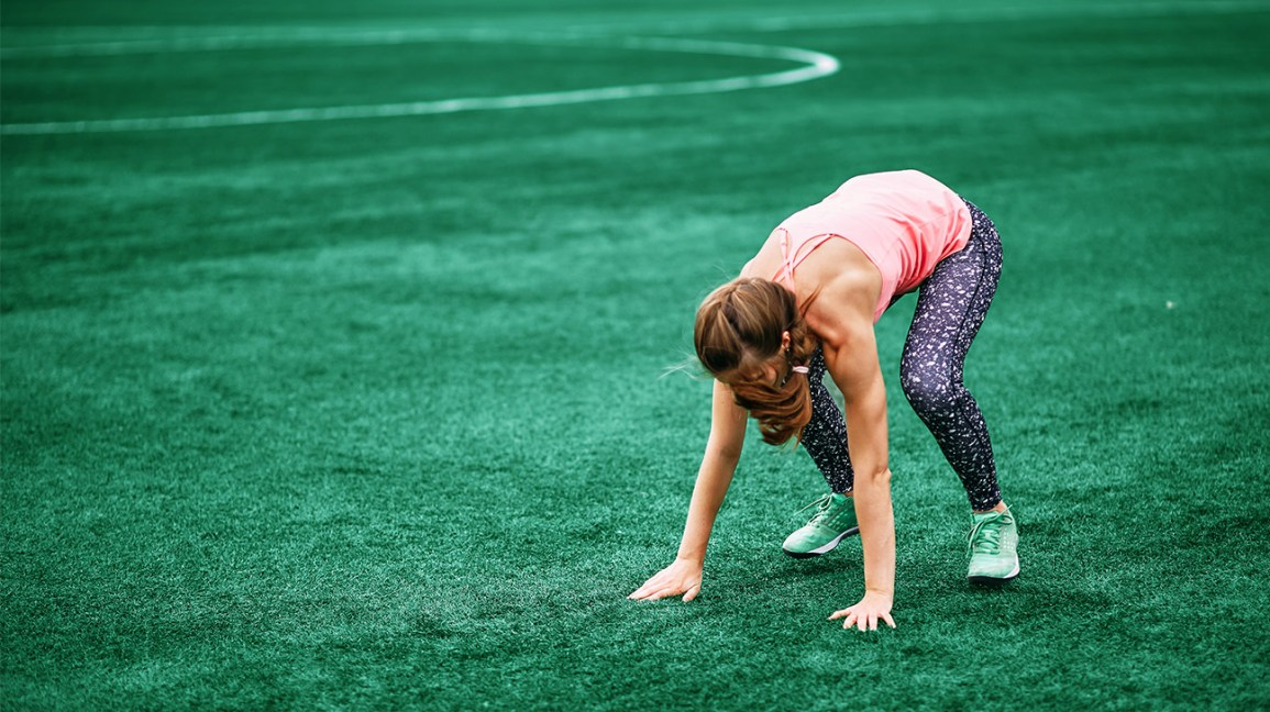 woman doing a burpee on grass