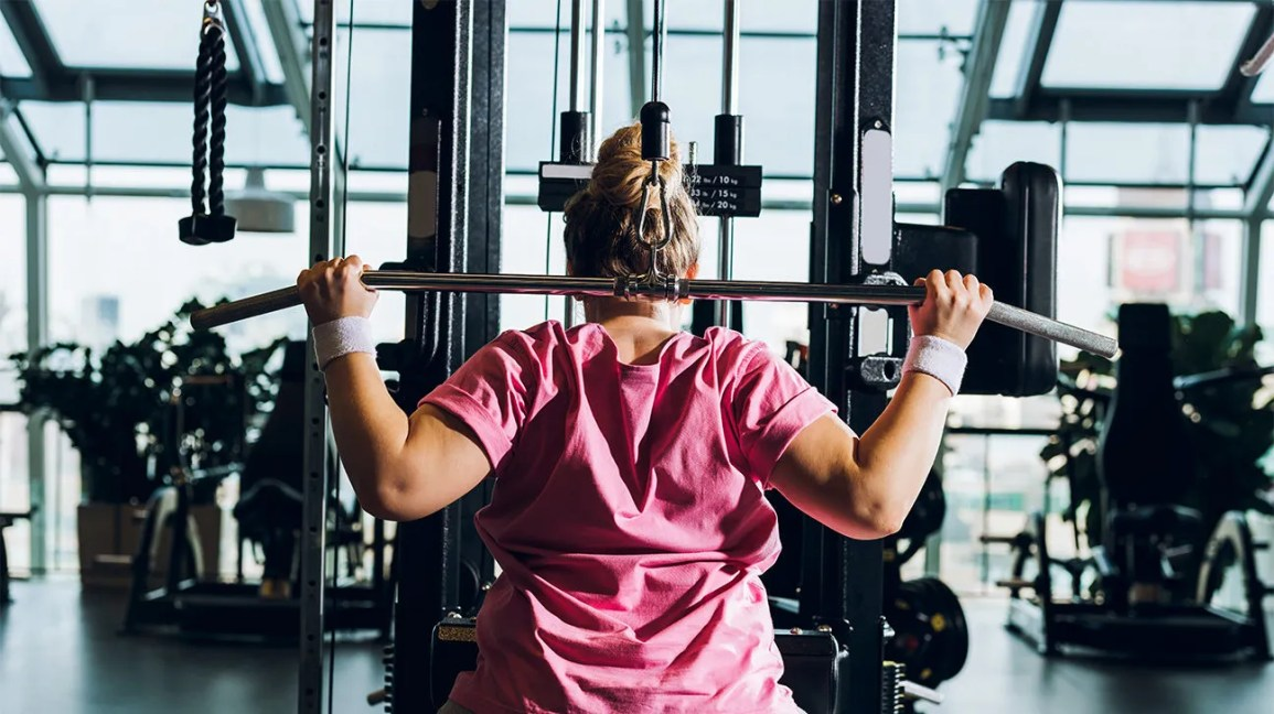 a woman using a gym machine wrong