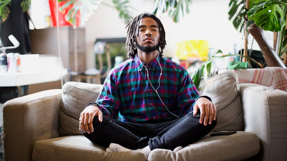 man meditating on couch