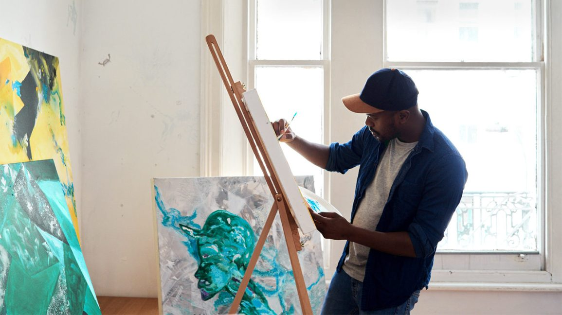 man painting on a canvas for stress relief