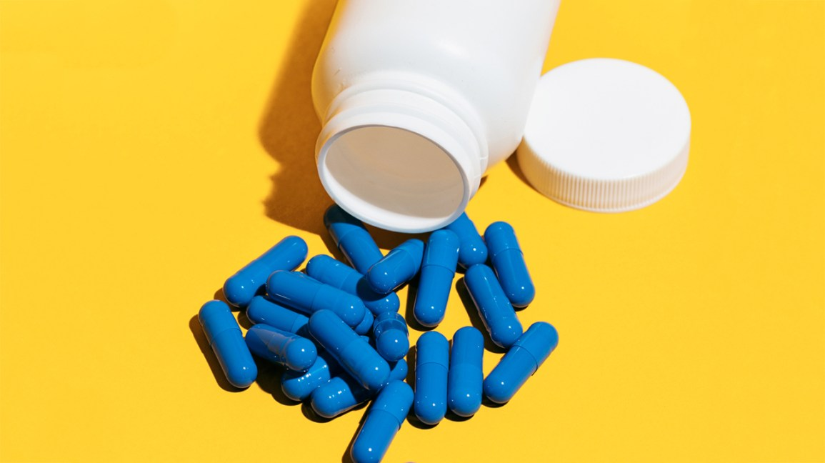 Blue Pills And Bottle On A Yellow Background