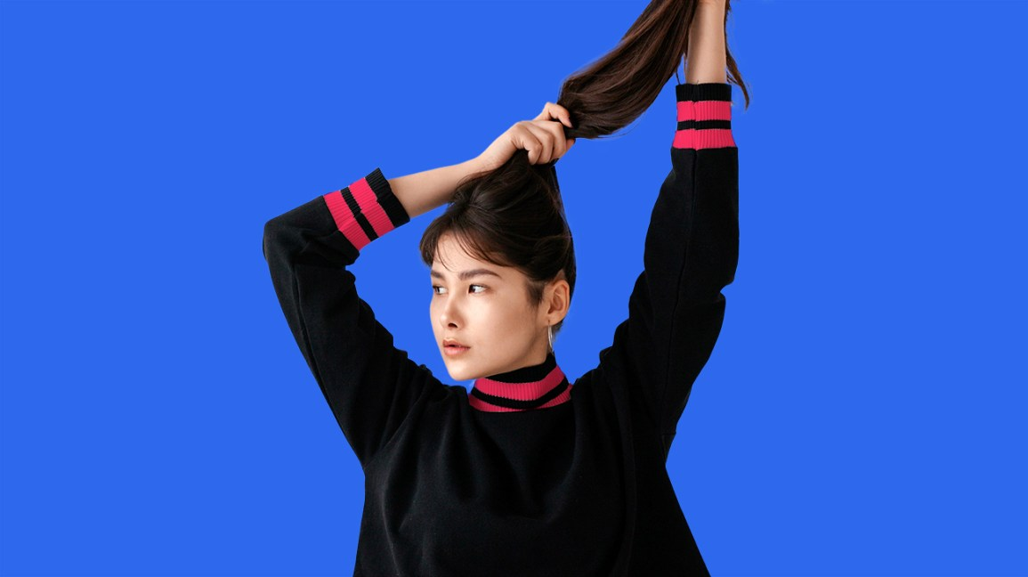 young woman holding hair up in a pony tail