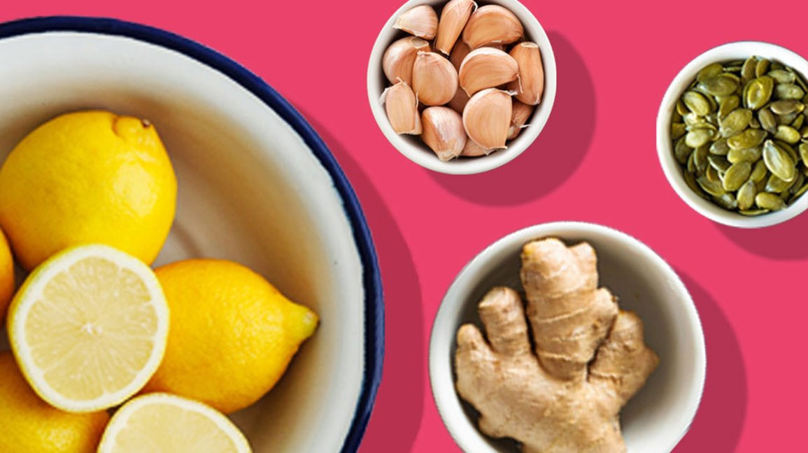 Ginger, lemon, sunflower seeds, and garlic on a hot pink background