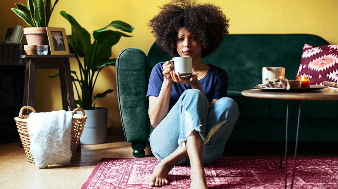 woman drinking tea against a couch