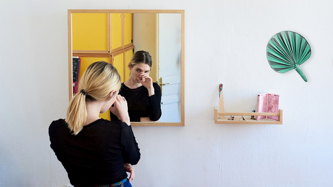 woman looking in the mirror with a hand covering her face