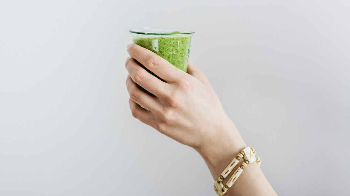 person holding a green smoothie