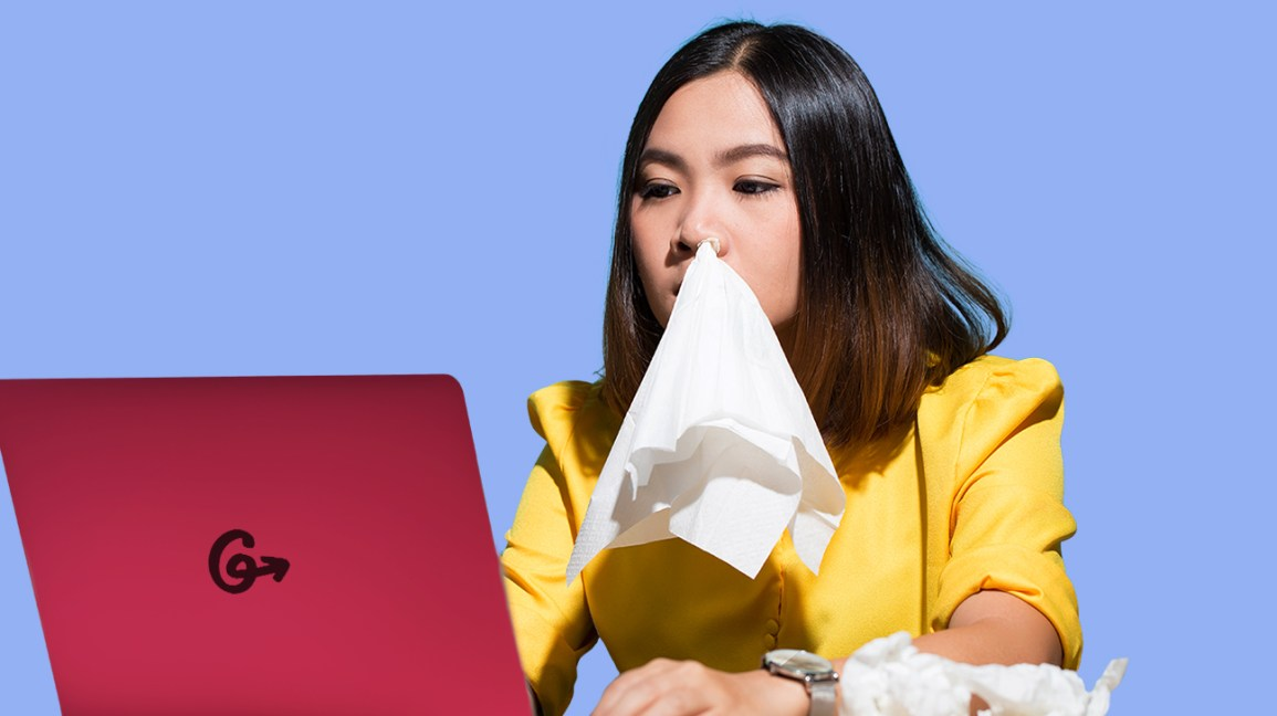 Girl with tissue in her nose, working on a computer