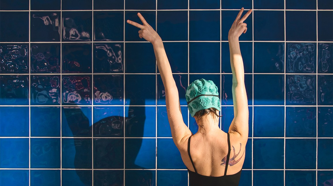 Back of young woman in swimming hat swimming vs running header
