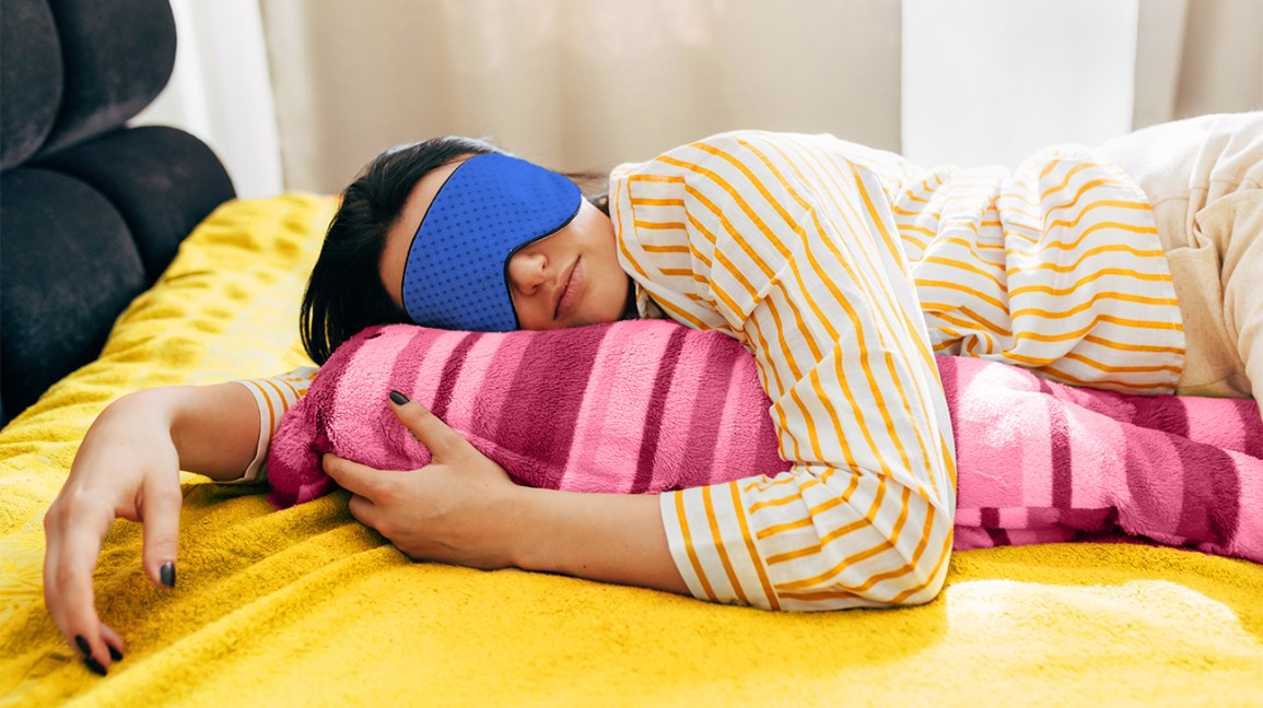 Image of heavy sleeping young woman lying on the bed with sleeping mask, having sweet dreams. Female lying on colorful pillow with blue sleep mask on her eyes resting at home header crop