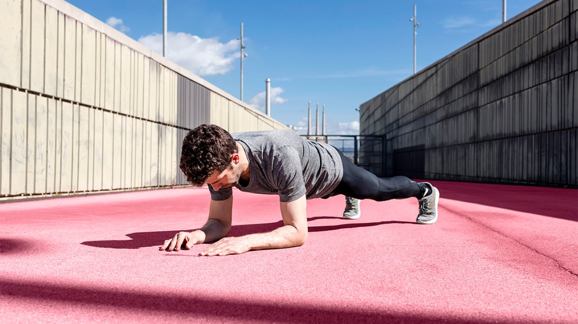 Sportive man exercising outdoors between walls exercising abs header crop