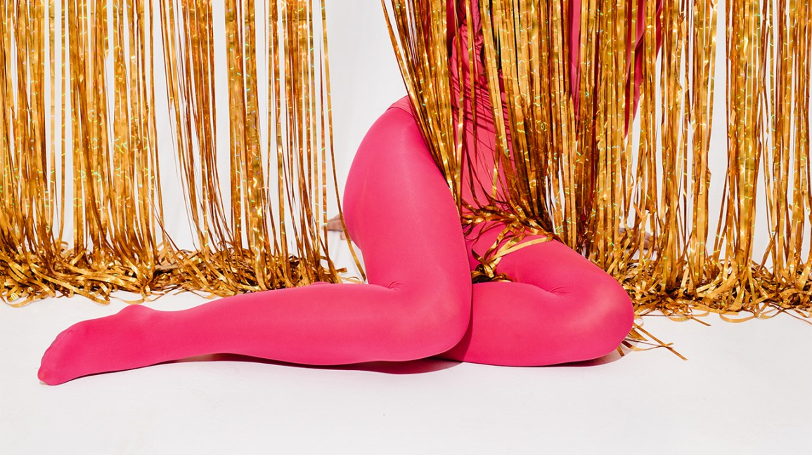 female legs in pink tights behind gold streamers
