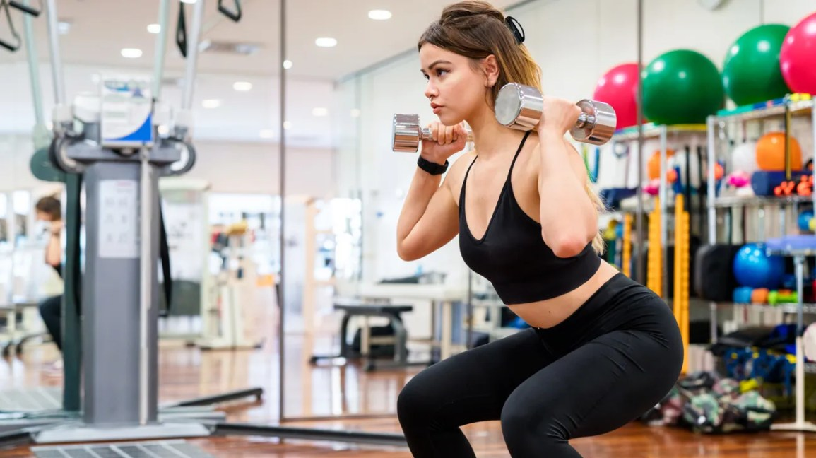 young woman squatting with dumbbells in a gym