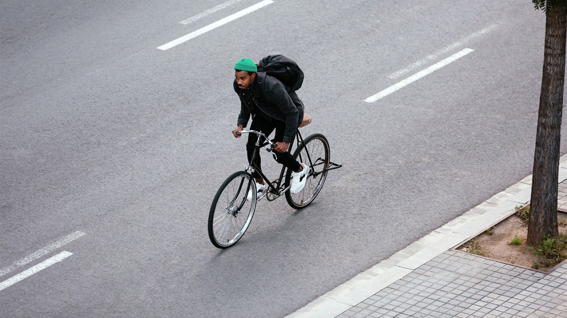 man rides bike in city header
