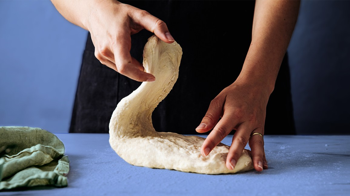close up on hands kneading dough to simulate yeast