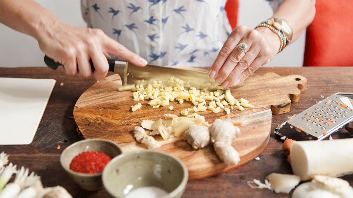 woman chopping raw ginger root on a wooden cutting board