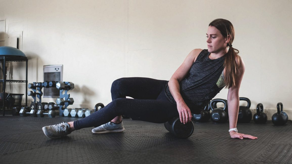 woman stretching glutes with roller