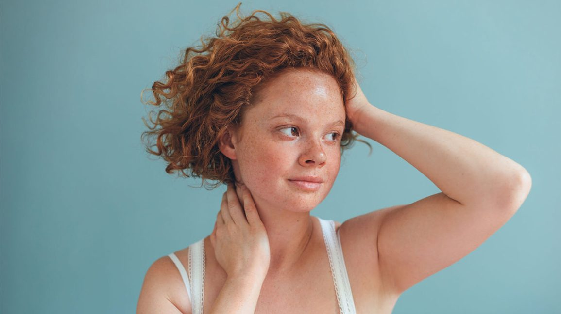 A head-and shoulders shot of a woman with curly red hair against a pale blue/gray background.
