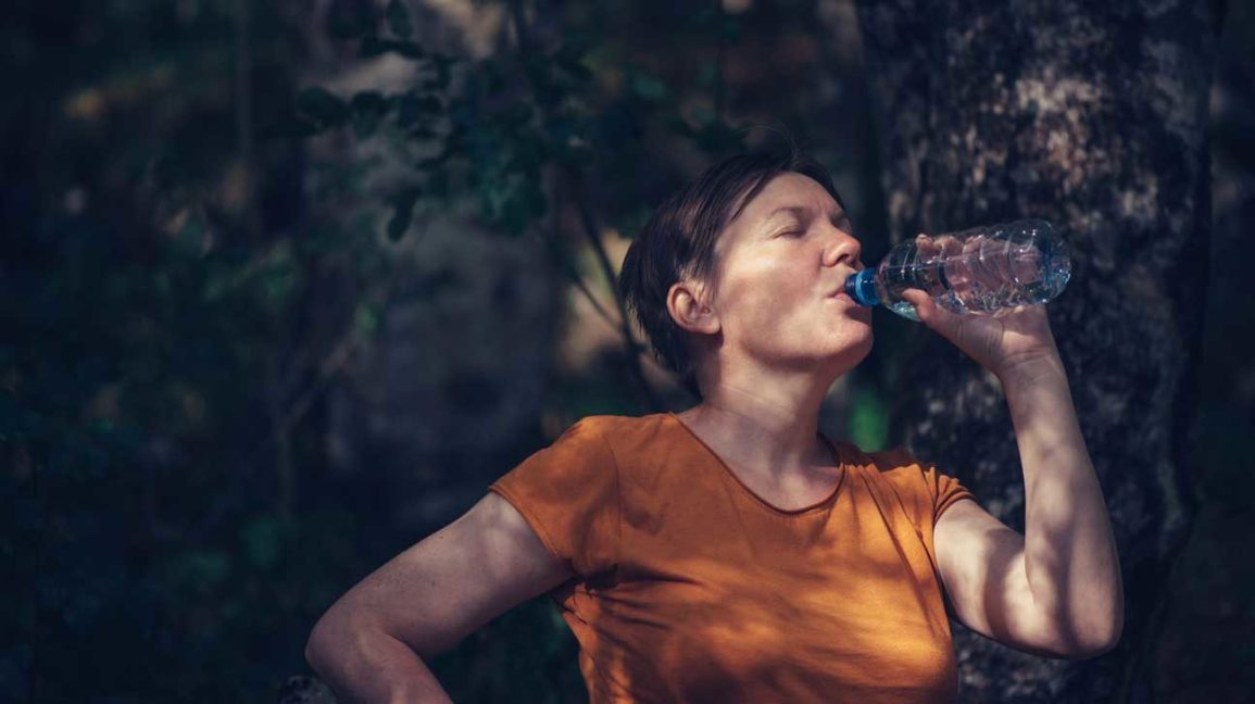 woman drinking water from bottle outside
