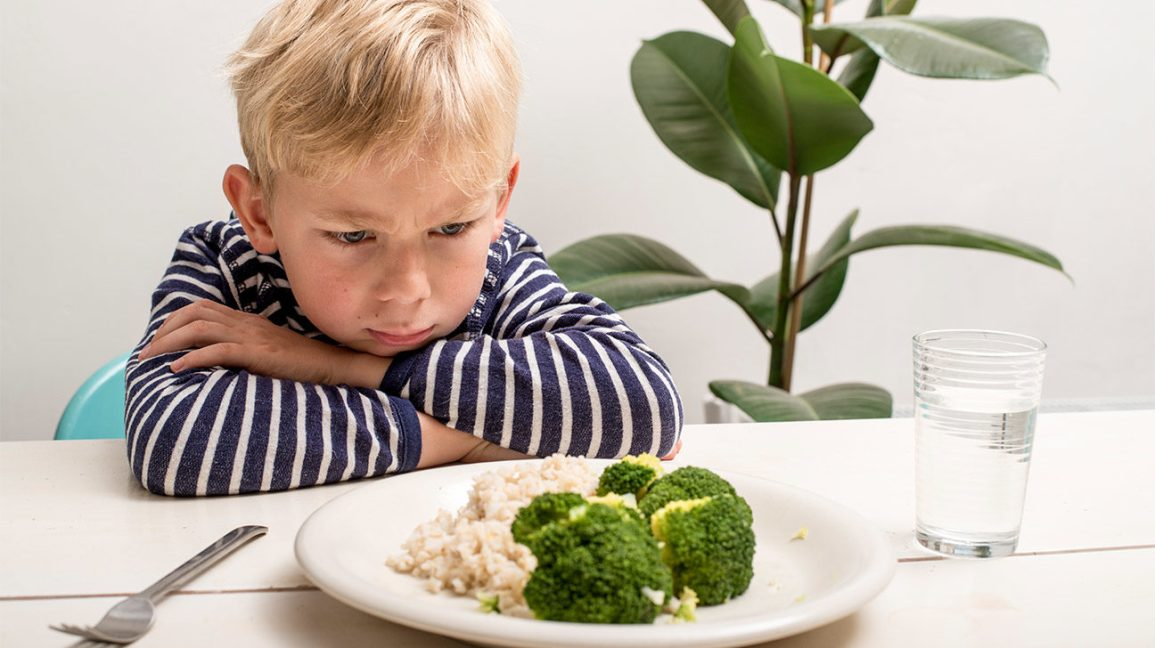 young child looks unhappily at broccoli due to picky eating