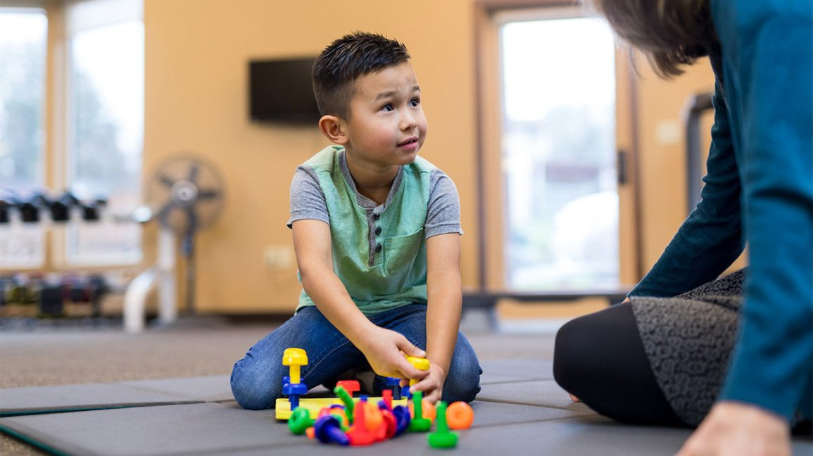 play therapy, young boy playing with toys with a therapist