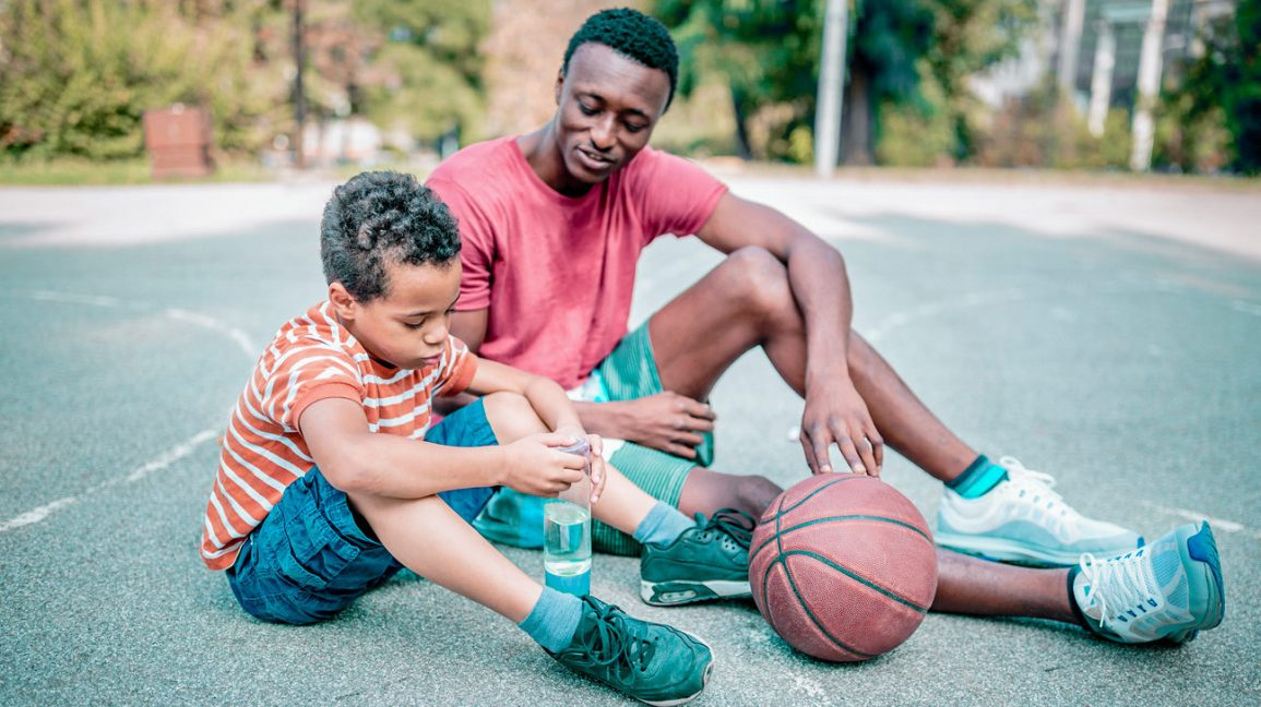 father and son sit and talk on basketball court