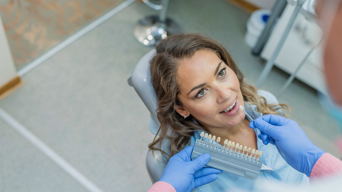 woman in a dentist's chair trying to select a veneer that matches her teeth