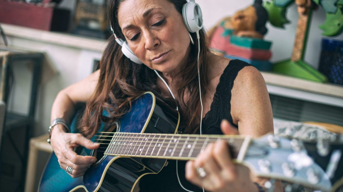 woman playing guitar as a way to exercise her brain