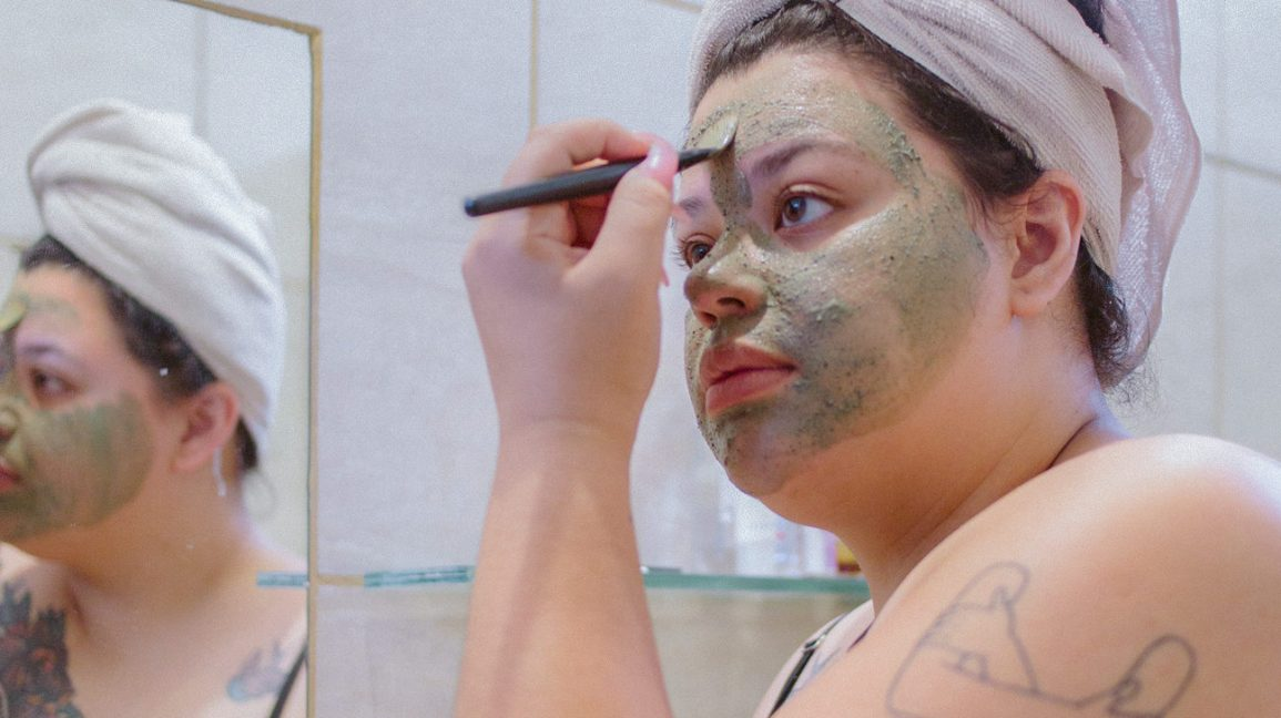 Woman applying a green tea face mask with a small brush.