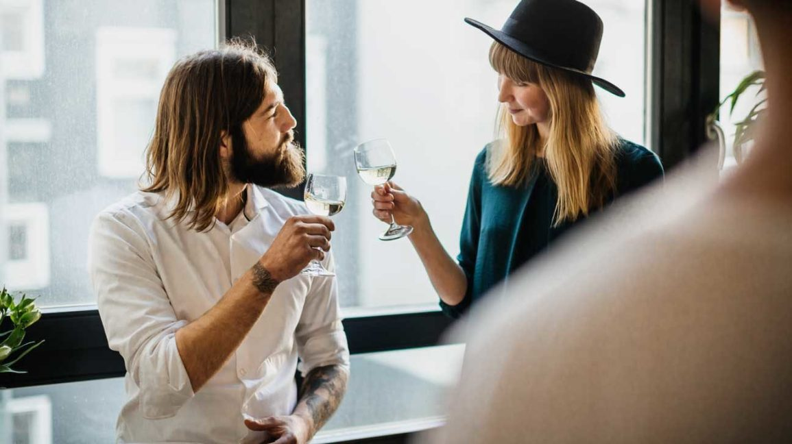 man and woman drinking white wine