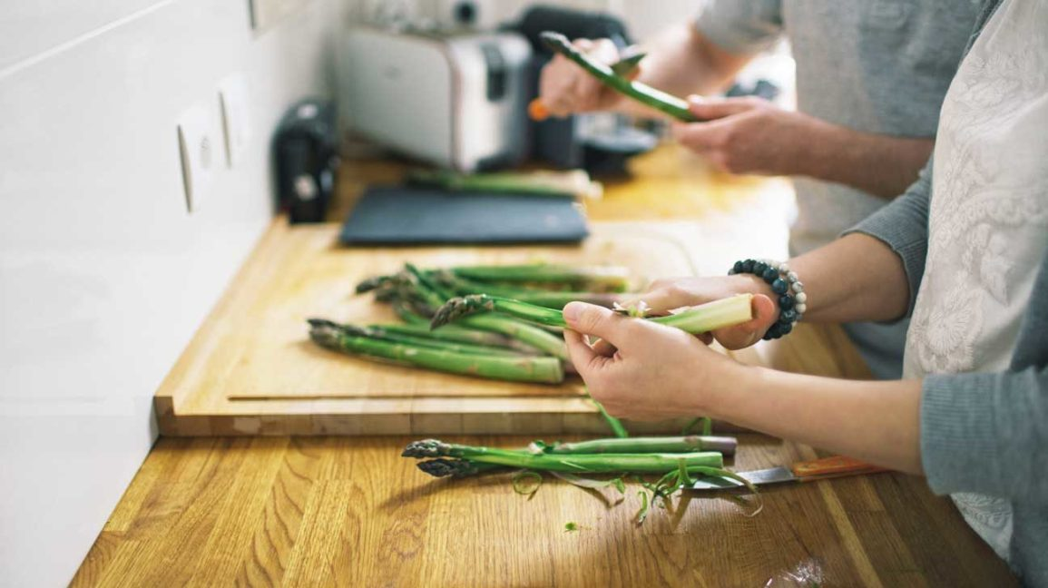 couple cutting raw asparagus