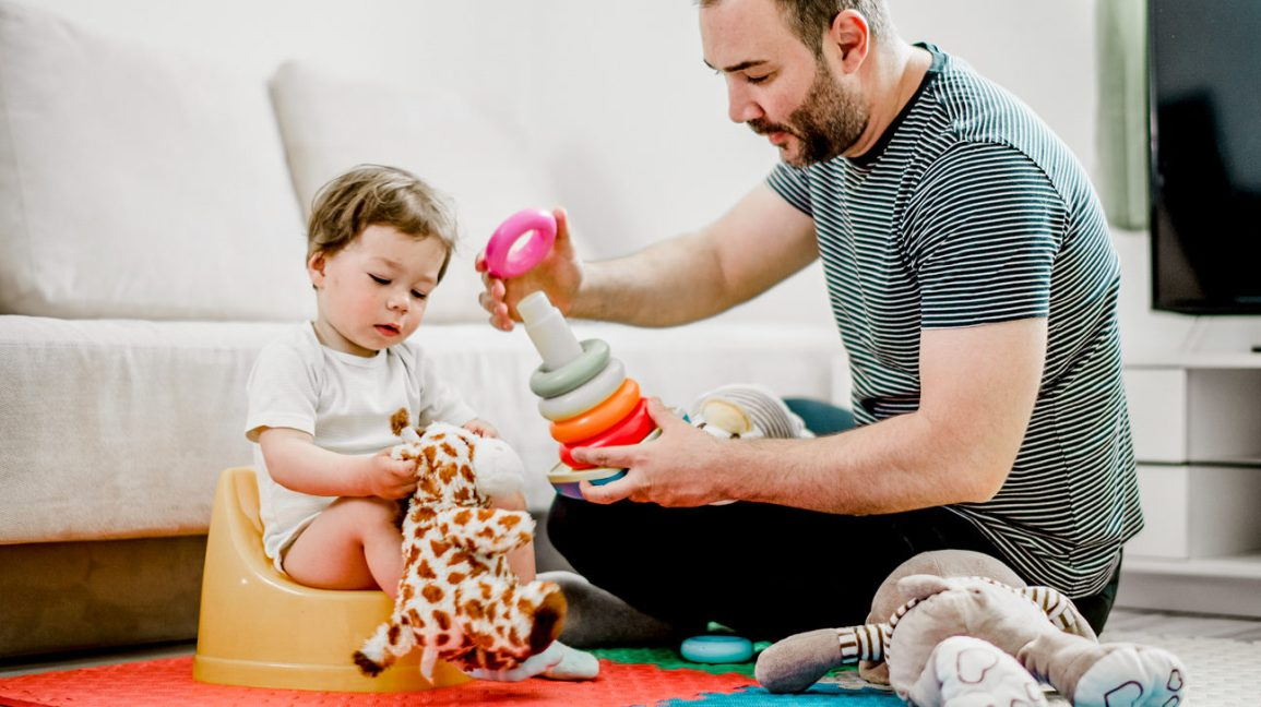 father and child play with toys while potty training