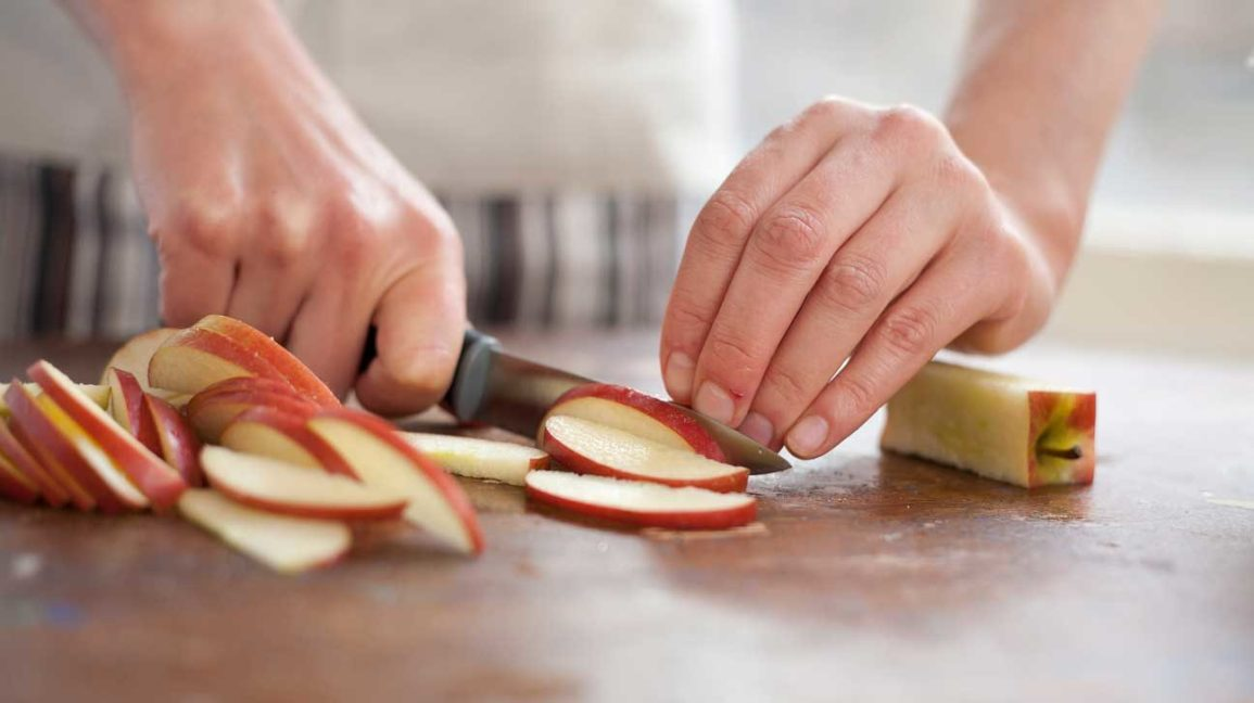 hands cutting an apple into slices