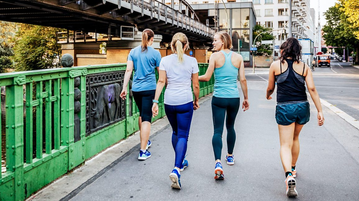 a group of friends walking together wearing workout gear