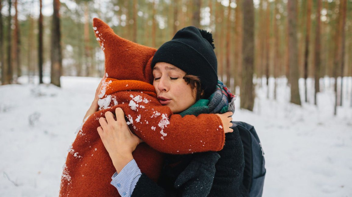 woman and child hugging outside in the snow