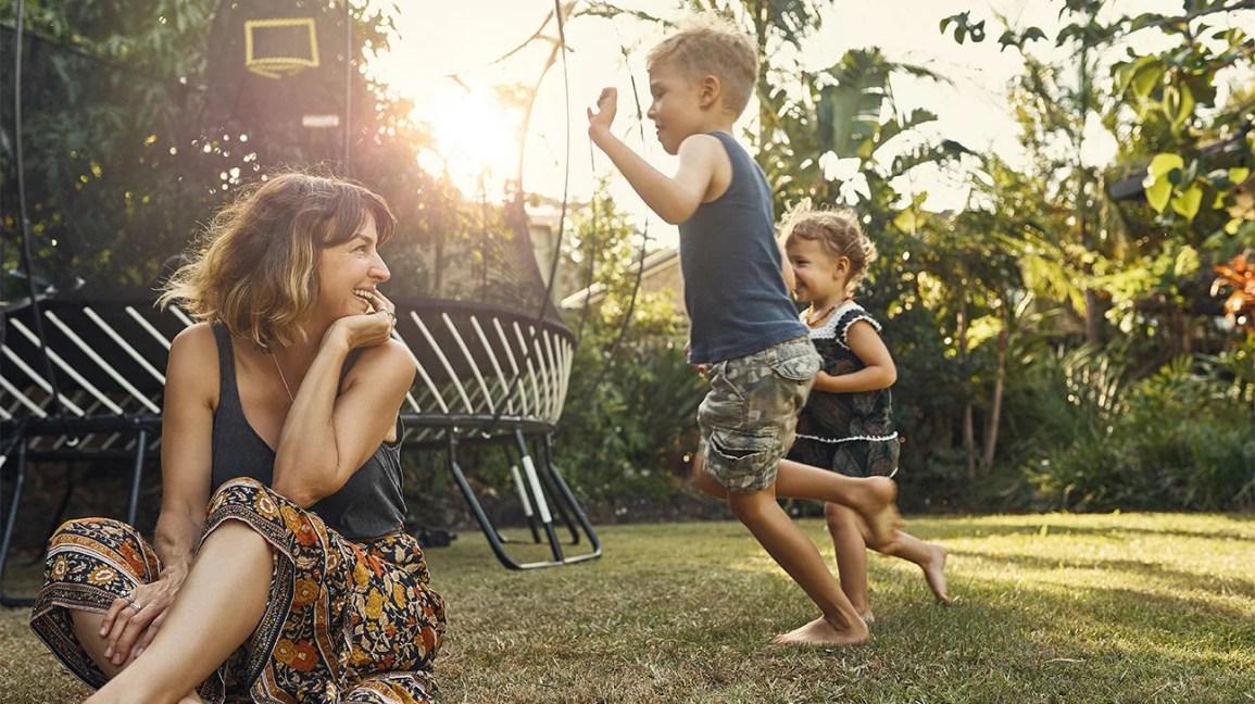 mãe e filhos em um quintal brincando