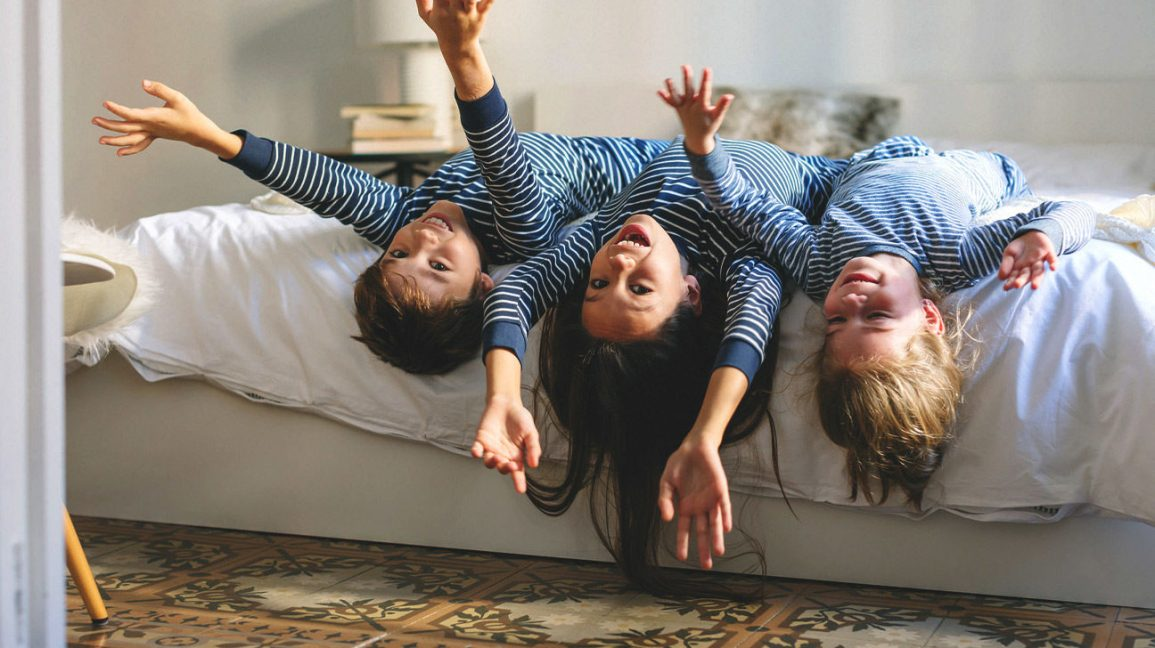 three children on a bed