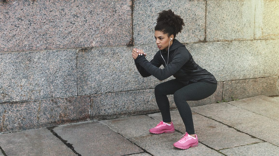 A woman doing a basic squat outdoors.