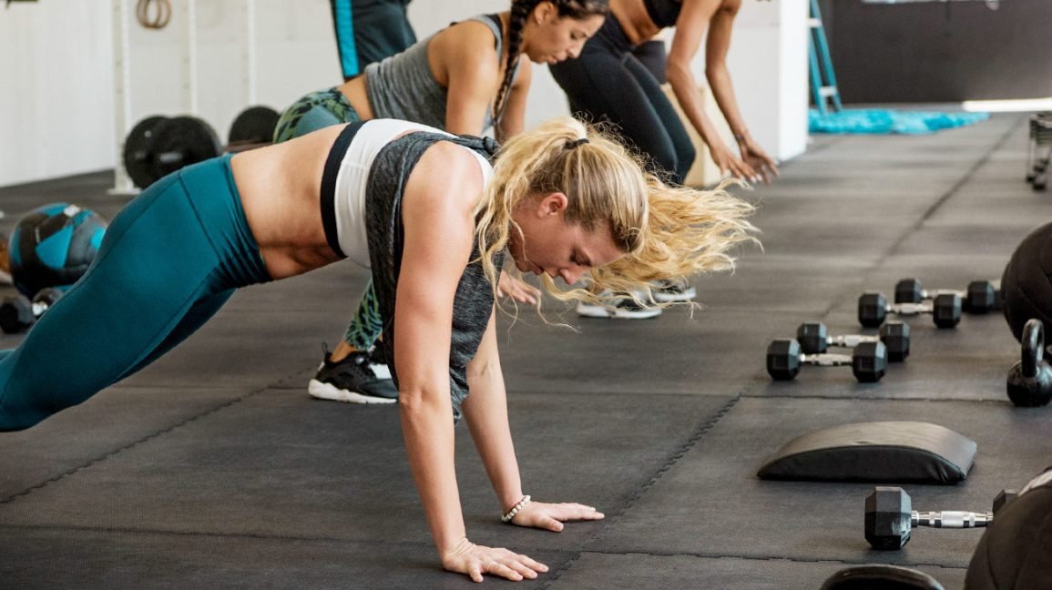 A woman in workout gear, at a gym, in the process of doing a burpee, with her hands on the floor