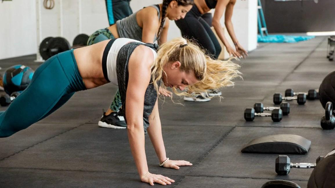 Uma mulher em equipamento de treino, em uma academia, no processo de fazer um burpee, com as mãos no chão