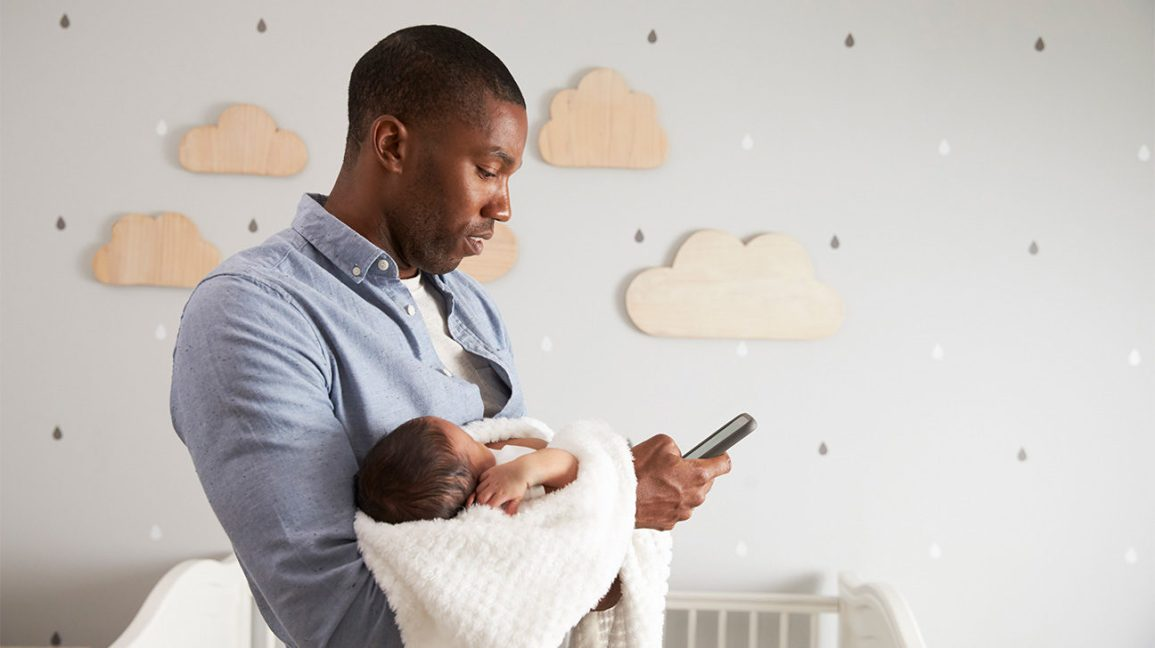 father consults his phone while holding newborn