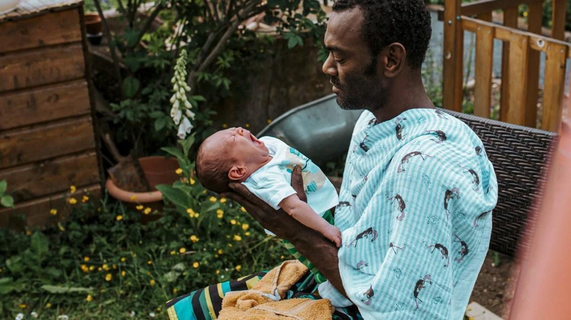 homem segurando bebê recém-nascido ao ar livre