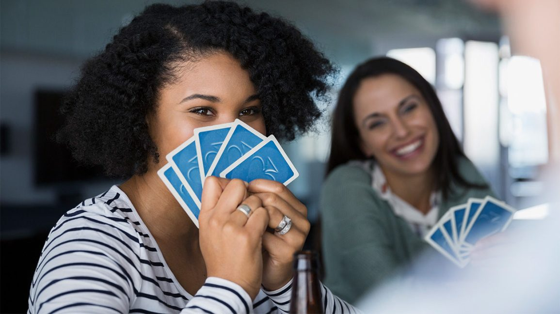 woman hiding face behind cards