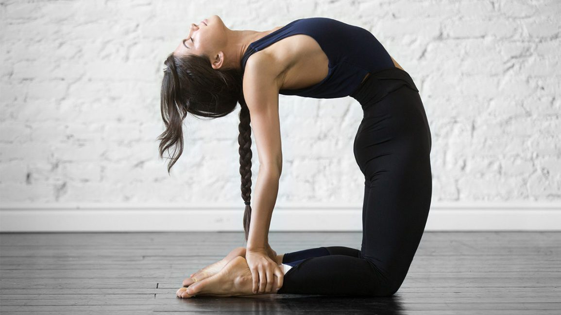 A young woman kneeling on the floor while arching her head and upper body backwards, and grabbing her feet. This is a version of rite number three of the 5 Tibetan Rites.