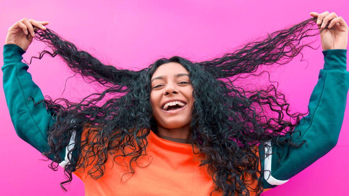 Uma pessoa feliz, com cabelos longos, grossos e ondulados, sorrindo contra um fundo rosa, enquanto segura as pontas dos cabelos.