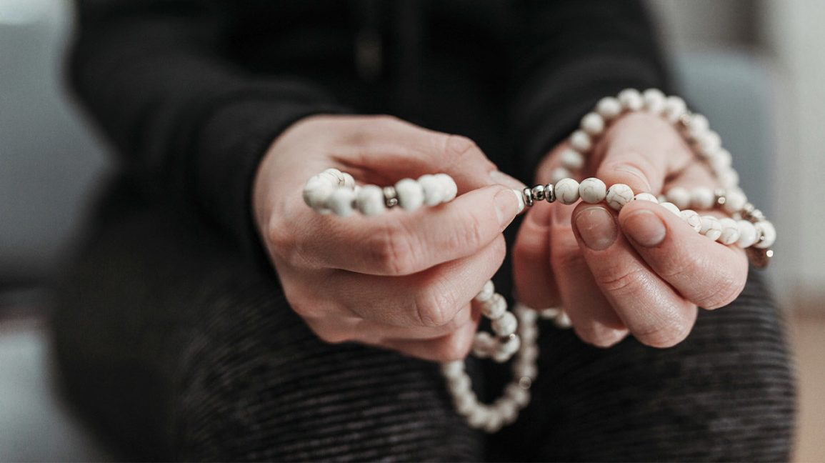 person holding mala beads