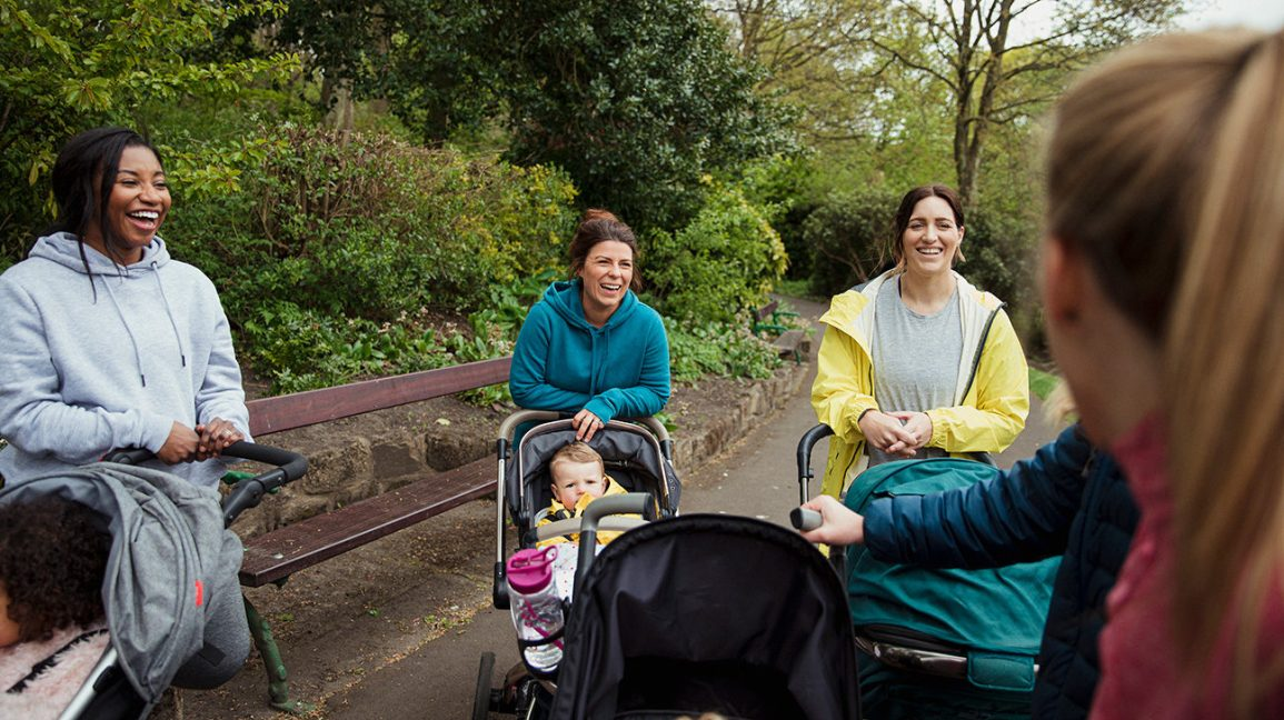 mom friends pushing strollers gather to talk