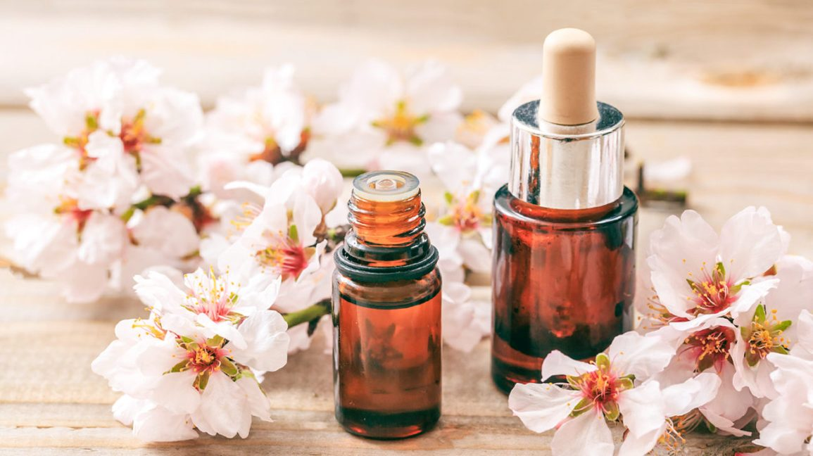 Two glass bottles of almond oil, one with a stopper and one open, surrounded by small white blossoms on a table top.
