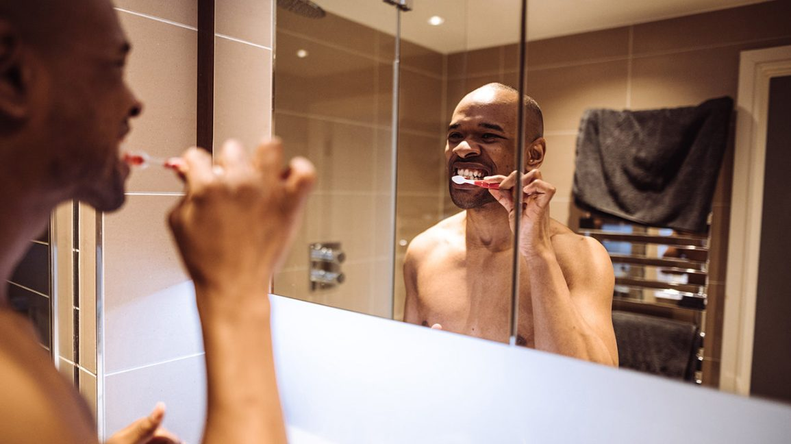 homem com dentes cinza, escovando os dentes